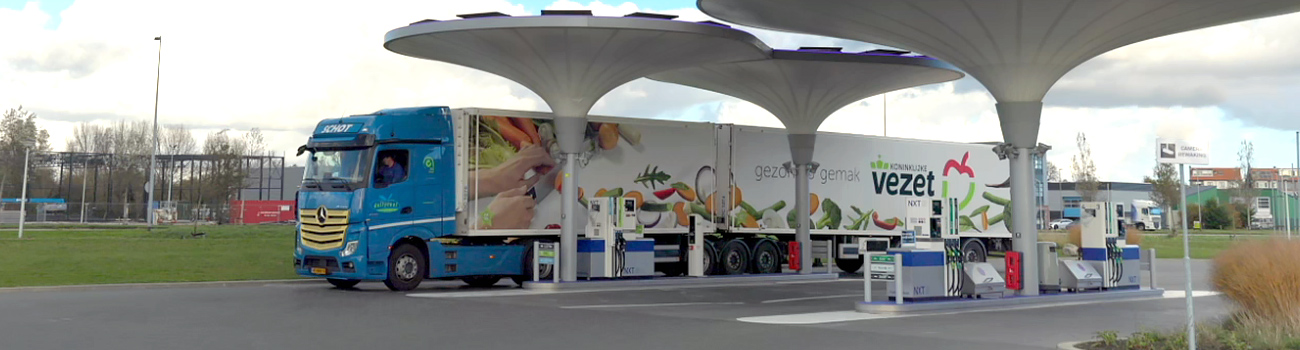 Zijaanzicht van een Dailycool vrachtwagen die geparkeerd staat bij een tankstation